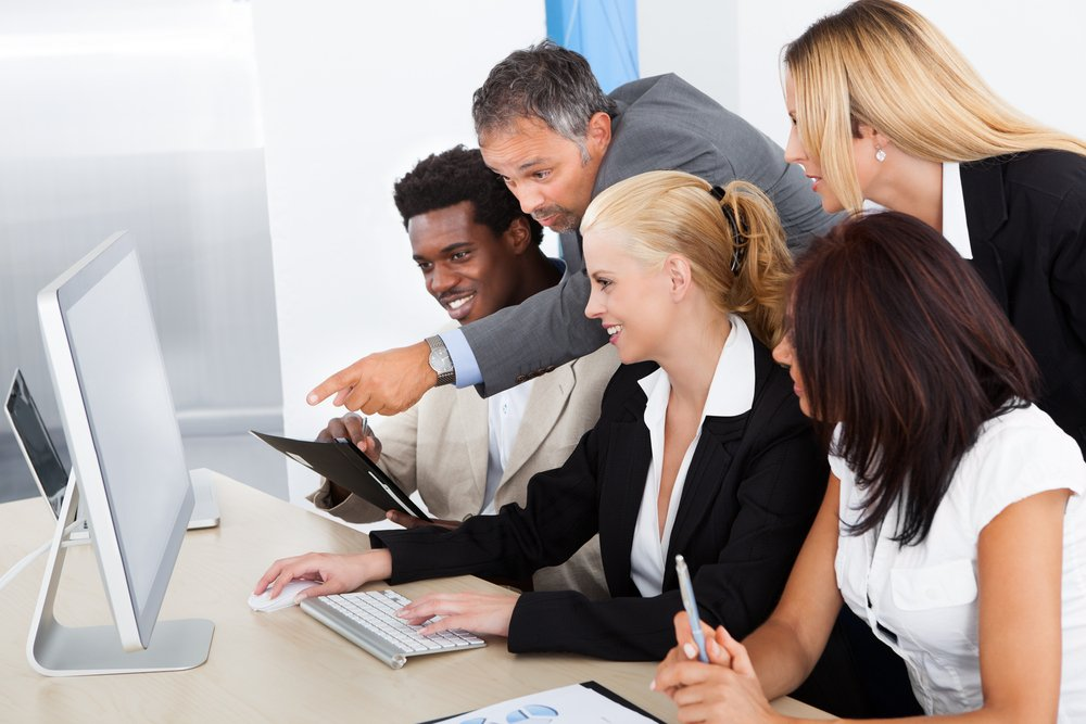 A group of employees looking at something humorous on the internet