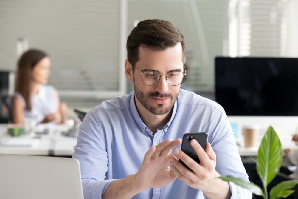 A male executive takes a break at work to play on his phone