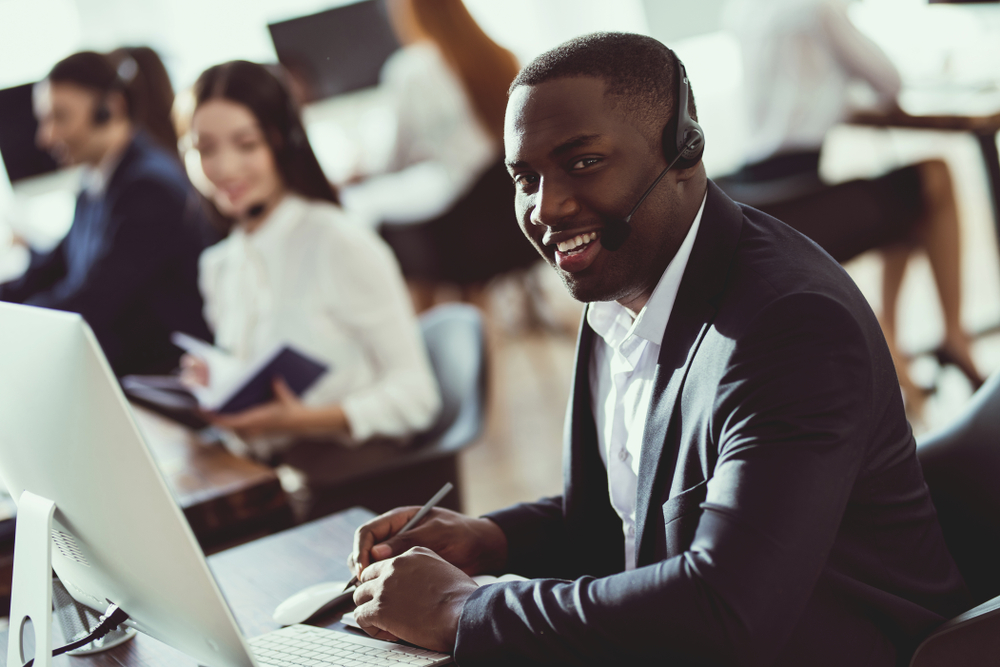 Happy call center employee wearing a headset